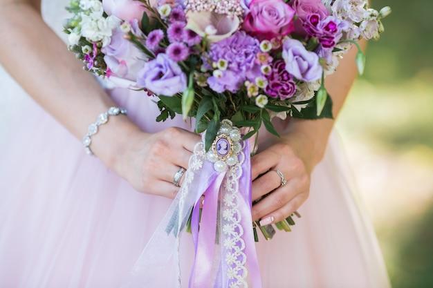 花嫁の手にさまざまな花を持つ美しい結婚式のカラフルな花束。ブライダルサマーブーケ