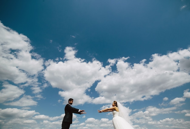 Beautiful wedding couple on the background of blue sky