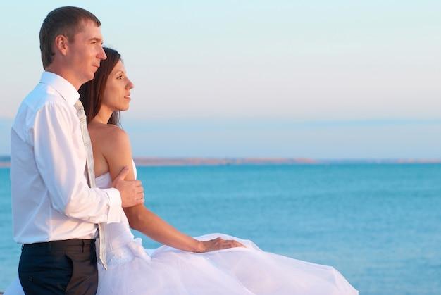 Красивая свадьба пара жених и невеста обнимаются на пляже