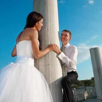 古代都市のギリシャの列の近くの美しい結婚式のカップルの新郎新婦