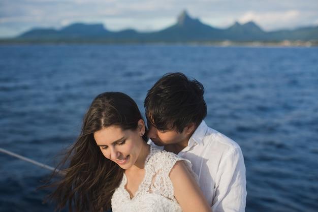 美しい結婚式のカップルの海で屋外の結婚式の日にヨットの上で新郎新婦。幸せな結婚カップルが海でボートにキスします。