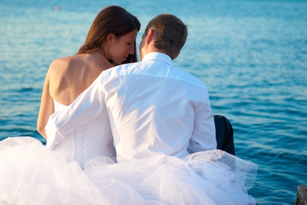 Beautiful wedding couple bride and groom hugging at the beach