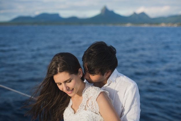 Beautiful wedding couple bride and groom on yacht at wedding day outdoors in the sea. happy marriage couple kissing on boat in ocean.