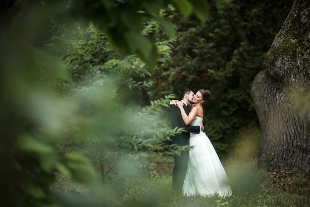 Beautiful wedding couple in each others arms in the park