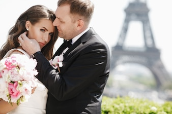 Beautiful wedding couple has fun posing on the square before the Eiffel Tower in Paris