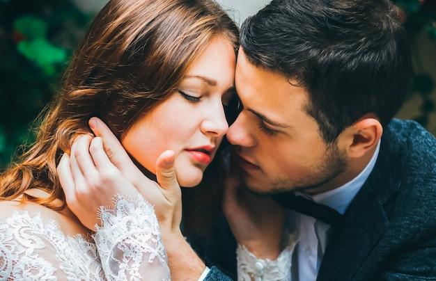 美しい結婚式のカップルが抱擁します。ハンサムな新郎は手にかわいい花嫁の顔を取ります。ロマンチックなラブストーリー。一緒に幸せな人々。