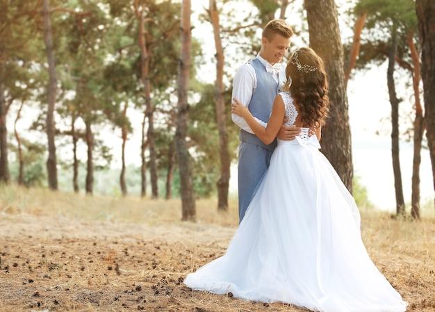 川の近くの針葉樹林の美しい結婚式のカップル