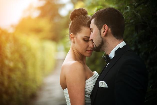 公園でお互いの腕の中で美しい結婚式のカップル、近い角度