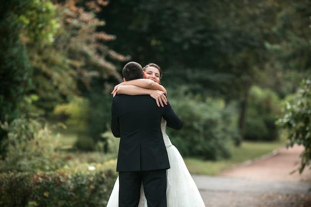 公園でお互いの腕の中で美しい結婚式のカップル