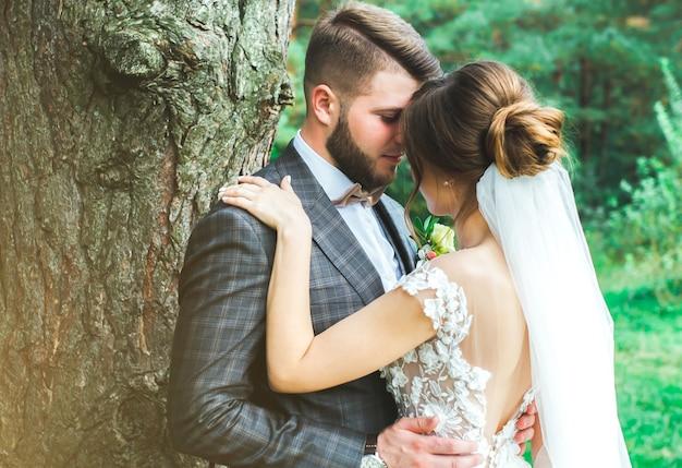 森の中の美しい結婚式のカップル。チュールベールとオープンローバックのエレガントなドレスを着た花嫁は、蝶ネクタイで新郎を抱いています。グレートギャツビースタイルのウェディングボタンホールとチェッカースーツ。