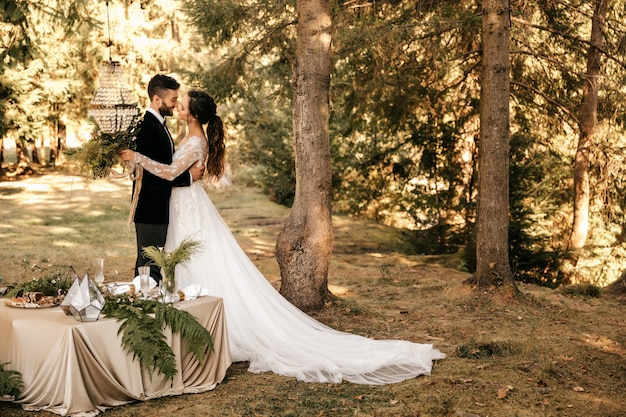 森の中の美しい結婚式のカップル。二人のための結婚式。素朴な装飾。