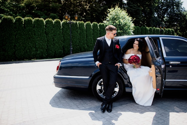 Beautiful wedding couple is smiling in the black car on the sunny day, dressed in elegant wedding outfits with red bouquet