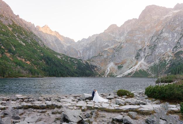 高山の湖の美しい景色の前に美しい結婚式のカップルが立っています。