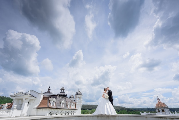 Beautiful wedding couple is standing near the church with beautiful cloudy sky