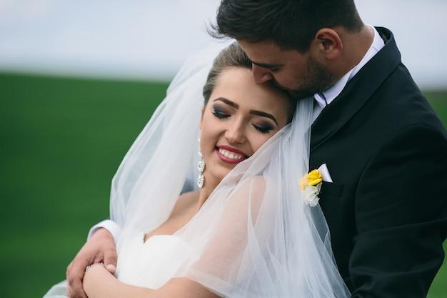Beautiful wedding couple is walking on the green field