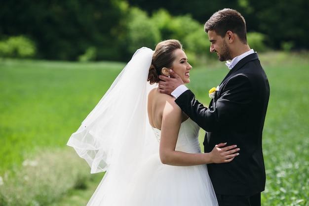 Bella coppia di sposi sta camminando sul campo verde