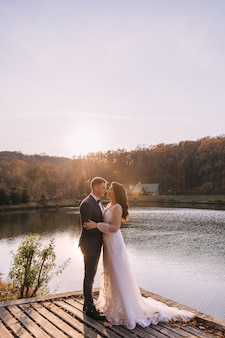 Beautiful wedding couple kisses and hugs on the banks of the river and beautiful nature