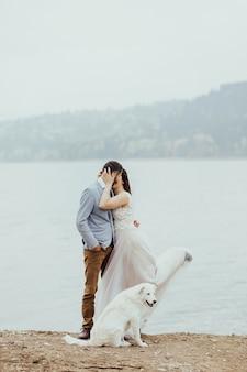 山の川の岸の近くでキスして抱きしめる美しい結婚式のカップル。幸せなカップルの隣には良い白い犬がいます。