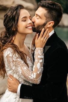 Красивая свадьба пара смеется и целуется на фоне камней.