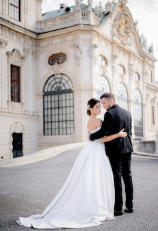 Beautiful wedding couple in love is standing together in front of historical architectural building