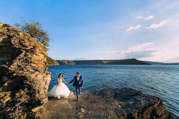 바위 해안에서 낭만적 인 산책에 아름다운 웨딩 커플