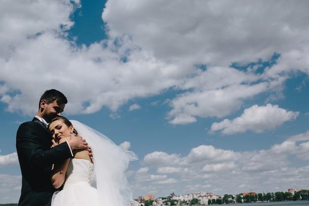 青い空、水を背景に美しい結婚式のカップル