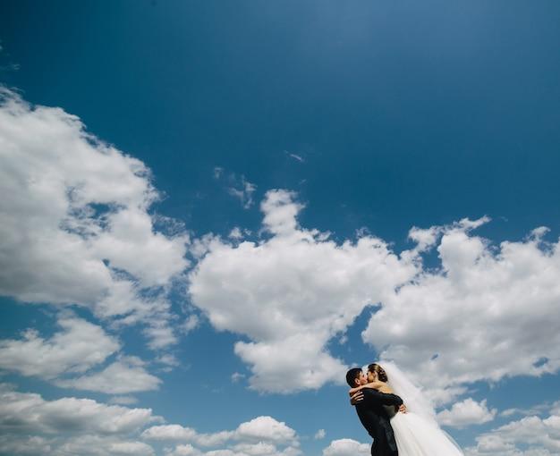 青い空を背景に美しい結婚式のカップル