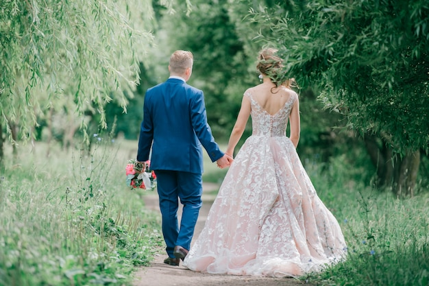 Beautiful wedding couple outdoor portrait from behind.