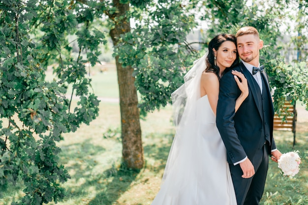 Beautiful wedding couple outdoor portrait. young pretty bride hugging groom at nature.  fine art lifestyle portrait of loving pair. wedding photosession. second half. just married. happy bridal day.