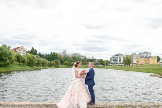 Красивая свадьба пара позирует для фотографа на природе