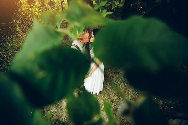 森の中でポーズをとって美しい結婚式のカップル