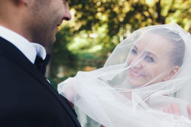 Красивая свадебная пара позирует в лесу