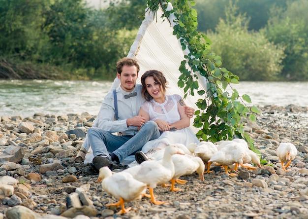 Красивая свадебная пара позирует на природе