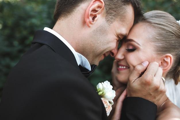 Красивая свадебная пара позирует в парке