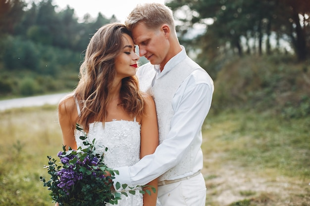 Beautiful wedding couple in a summer field