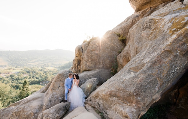 Beautiful wedding couple on the sunny day is standing on the huge rocks with picturesque view of a forest