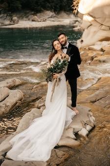 美しい結婚式のカップルは、山の川、花嫁の長い白いドレスの背景に優しく抱擁します。