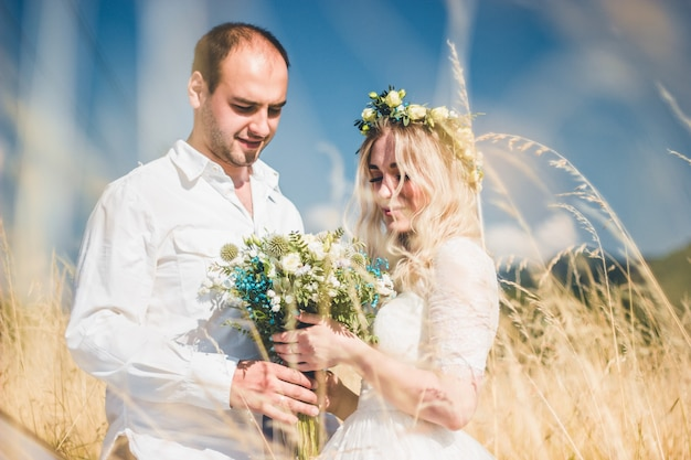 Beautiful wedding couple walking on field, bride and groom posing on wheat field with blue sky.