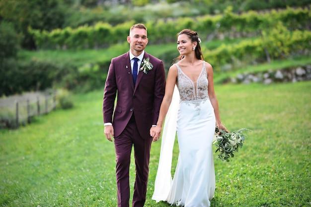 美しいブドウ園を歩く美しい結婚式のカップル