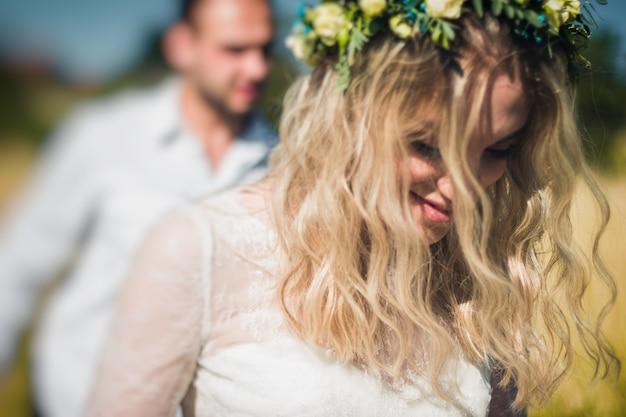 フィールド上を歩く美しい結婚式のカップル、青空と麦畑でポーズをとる新郎新婦。