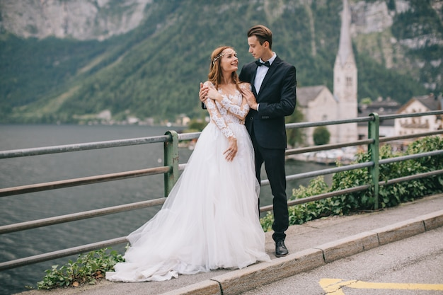 A beautiful wedding couple walks on a background old cathedral in a fairy austrian town