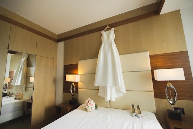 Beautiful wedding dress on hanger in room