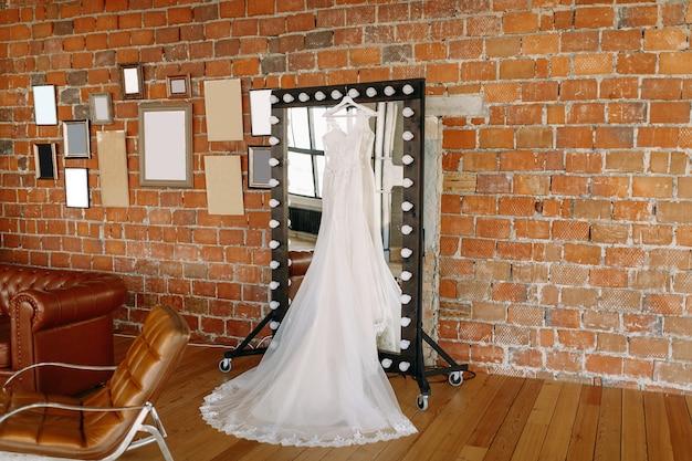 Красивое свадебное платье висит на зеркале в большом зале у кирпичной стены
