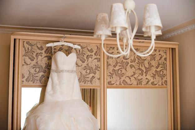 Beautiful wedding dress hanging on a wardrobe