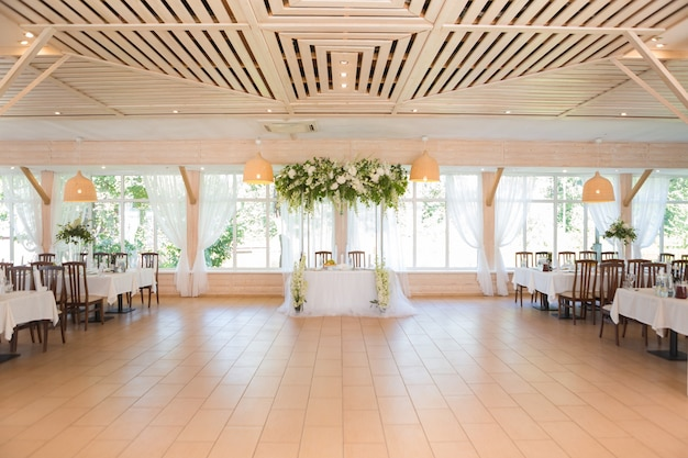 Beautiful wedding floral decoration on a table with catering food in a light restaurant hall with white tablecloths