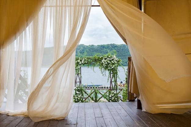 緑の葉と白いバラと小枝の美しい結婚式のフラワーアレンジメントの結婚式のアーチ