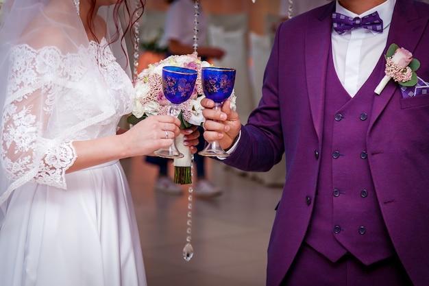 結婚式で新婚夫婦の手にシャンパンの美しい結婚式のグラス