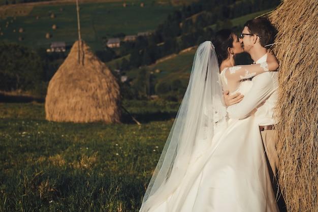 山での美しい結婚式、干し草のロフトの近くの若い幸せなカップル。
