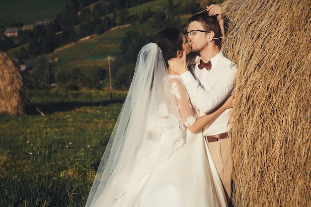 山の美しい結婚式、干し草の近くの若い幸せなカップル。