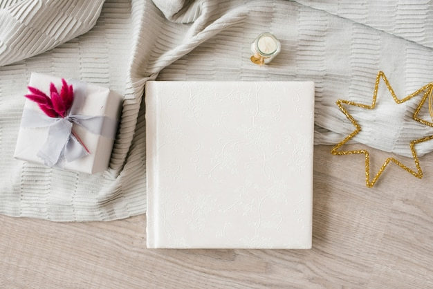 Beautiful wedding photo book cover in leather with embossed lace surrounded by gift box and stars